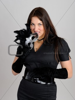 Beautiful sexy woman in black dress in party carnival mask