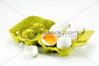 Broken egg in the box on a white background