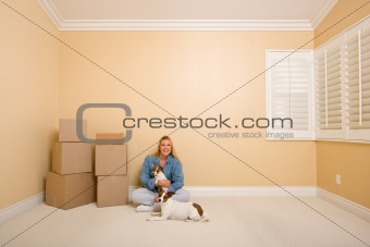 Pretty Woman and Dogs Sitting on the Floor with Moving Boxes in Empty Room
