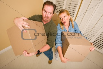 Obviously Exhausted Couple Holding Moving Boxes in Empty Room.