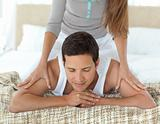 Relaxed man being massaged by his girlfriend on their bed