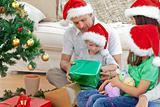 Happy family looking at the little boy opening a christmas prese