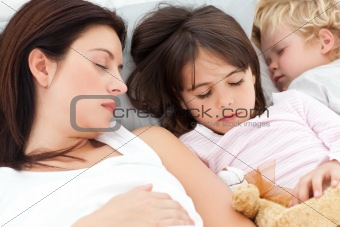 Adorable brother and sister sleeping with their mother in her be