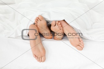 Close up of couple's feet while having fun in their bed