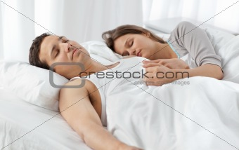 Cute couple sleeping together on their bed