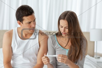Worried couple looking at a pregnancy test sitting