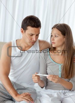 Man looking at a pregnancy test with his girlfriend