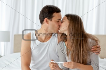 Couple kissing after looking at the result of a pregnancy test