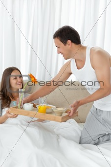 Attentive man bringing the breakfast to his girlfriend on the be