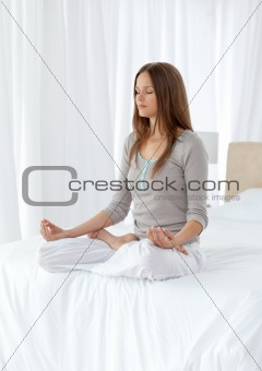 Quiet woman doing yoga exercises on the bed