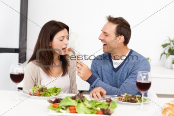 Attentive man giving a tomato to his girlfriend while having lu