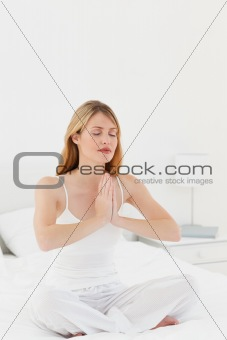 Beautiful woman practicing yoga on her bed