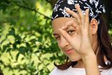 Teenage girl looking through ok sign
