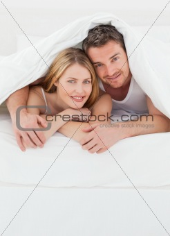 Lovely pair hugging  in their bed