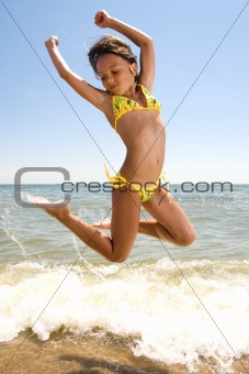 Little girl jumping at the seaside