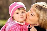 Mother kissing her little girl