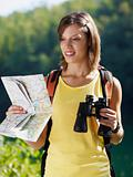woman hiking with binoculars and map