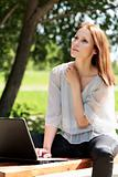 Pretty young woman with a laptop at park.