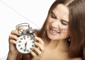 scared girl holding an alarm clock in the hands