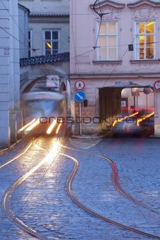 prague - cars and tramways passing under buildings at mala strana