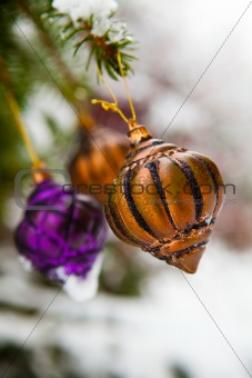 Christmas baubles on a snowy pine
