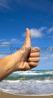 Thumb up hand sign with beach background