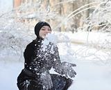 Portrait of cute young woman playing snowball outdoor in winter