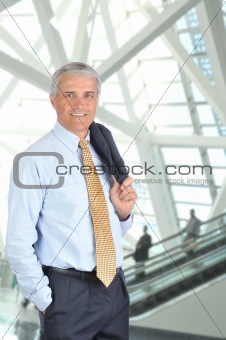 Businessman in lobby with escalator
