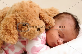 baby sleeps with brown toy dog on her back
