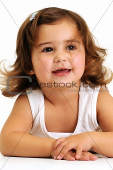 Little girl looking and smiling whilst leaning on her arms