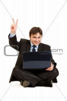 Smiling  businessman sitting on floor with laptops and showing victory gesture
