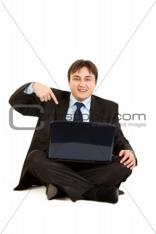 Smiling businessman sitting on floor and pointing finger at laptop