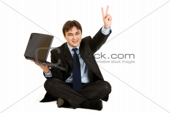 Sitting on  floor with laptop smiling businessman showing victory gesture