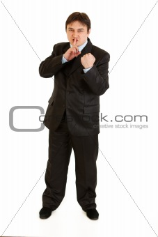 Angry  businessman with finger at mouth and threaten with fist
