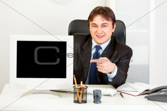 Smiling  businessman sitting at office desk and pointing finger at  monitor with blank screen