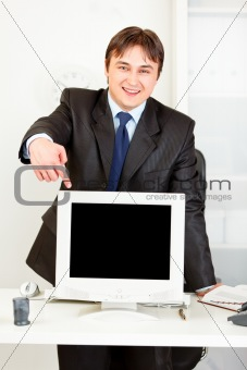 Smiling  businessman standing behind office desk and pointing finger at  monitor with blank screen