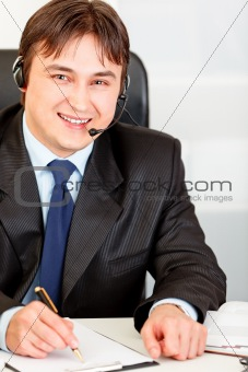 Smiling  businessman with  headset sitting at office desk and taking notes on paper