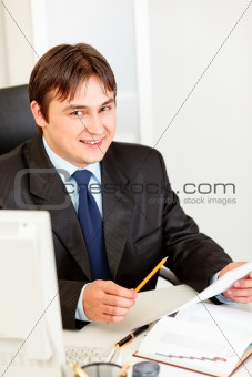 Smiling businessman sitting at office desk and working with documents