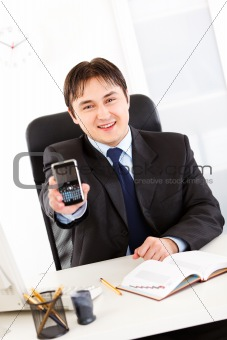 Smiling  businessman sitting at office desk and holding mobile phone with blank screen
