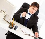 Concentrated businessman with cup of tea sitting at office desk and checking timetable in diary