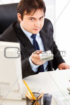 Smiling  businessman sitting at office desk and giving dollars packs
