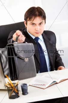 Attentive businessman sitting at office desk and giving briefcase