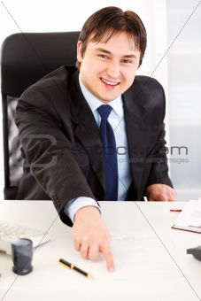 Smiling  businessman sitting at office desk and pointing on document for signature