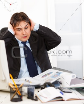 Shocked young businessman sitting at office desk  being overloaded with loads of work