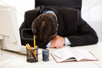 Tired businessman sleeping at  desk in  office