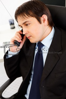 Attentive  young businessman talking on  telephone in office