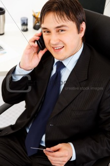 Smiling  businessman in office making purchase by phone and credit card
