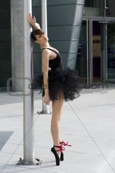 ballerina in black tutu near a pole