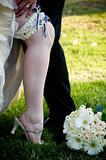 Groom€™s hand on bride's leg with blue and white garter exposed