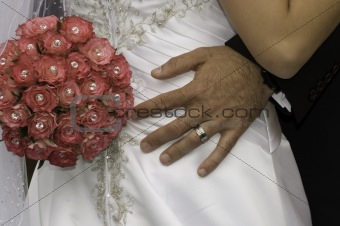 groom standing with his hand red bouquet on his brides bum